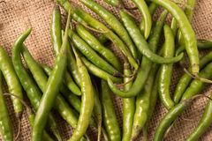 Spicy green hot chili peppers over burlap. Stock Photo