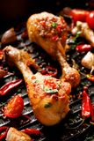 Spicy grilled chicken legs, drumsticks with the addition of chili peppers, garlic and herbs on the grill plate, close-up. Spicy grilled chicken legs, drumsticks royalty free stock images