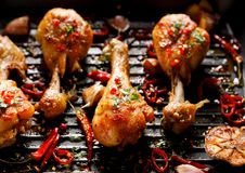 Spicy grilled chicken legs, drumsticks with the addition of chili peppers, garlic and herbs on the grill plate, top view. Spicy grilled chicken legs, drumsticks royalty free stock photo
