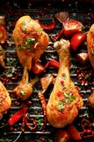 Spicy grilled chicken legs, drumsticks with the addition of chili peppers, garlic and herbs on the grill plate, close-up. Spicy grilled chicken legs, drumsticks royalty free stock photos