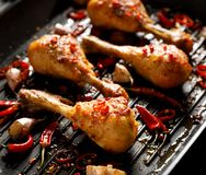 Spicy grilled chicken legs, drumsticks with the addition of chili peppers, garlic and herbs on the grill plate, close-up. Grilled food royalty free stock image