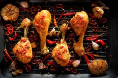 Spicy grilled chicken legs, drumsticks with the addition of chili peppers, garlic and herbs on the grill plate, top view. royalty free stock photos