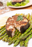 Spicy grilled halibut fish with asparagus. Serving of spicy broiled halibut garnished with asparagus and lemon close up stock images