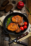 Spicy grilled pork chops in skillet stock images