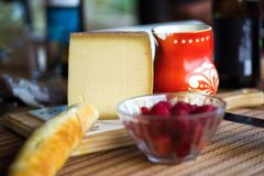 Cheese, bread, raspberry and red jug. Spicy hard cheese, long bread, raspberry in glass and red old pitcher with flower ornaments on kitchen table. Healthy Stock Photos