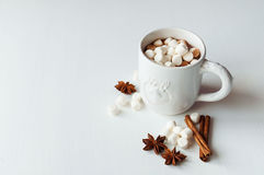 Spicy hot cocoa with marshmallows. In a white mug on a white background Stock Photography