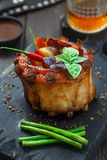 Spicy hot grilled crown ribs served on an old vintage wooden cutting board with vegs inside Royalty Free Stock Images