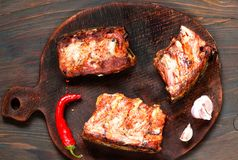 Spicy hot grilled spare ribs from BBQ served with  hot chili pepper and lime on dark wooden background. stock photos