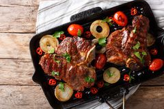 Spicy hot T Bone Steak with tomato, chili and onion in a grill p Royalty Free Stock Photo
