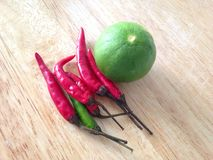 Spicy ingredients. Lime and chili with wood background Stock Photography