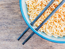 Spicy instant noodles in bowl with chopsticks Royalty Free Stock Photo
