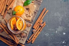 Spicy mandarines beverage in jar with cloves, anise and cinnamon. Selective focus. Shallow depth of field stock image