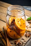 Spicy mandarines beverage in jar with cloves, anise and cinnamon. Selective focus. Shallow depth of field stock photos