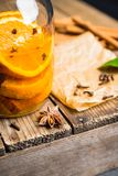 Spicy mandarines beverage in jar with cloves, anise and cinnamon. Selective focus. Shallow depth of field stock photography