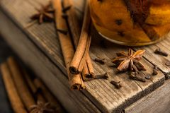 Spicy mandarines beverage in jar with cloves, anise and cinnamon. Selective focus. Shallow depth of field stock photo