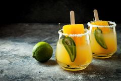 Spicy mango popsicle margarita cocktail with jalapeno and lime. Mexican alcoholic drink for Cinco de mayo party. Spicy mango popsicle margarita cocktail with royalty free stock images
