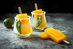 Spicy mango popsicle margarita cocktail with jalapeno and lime. Mexican alcoholic drink for Cinco de mayo party. Spicy mango popsicle margarita cocktail with stock images
