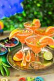 Spicy margarita. Spicy grapefruit margarita on ice in margarita glasses on the table in the garden Royalty Free Stock Photography