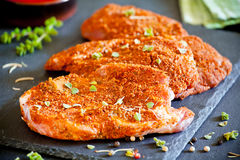 Spicy Marinated Pork Chops. Three marinated pork chops on a slate plate Royalty Free Stock Photography