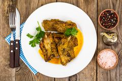 Spicy meat ribs in mustard sauce on wooden table stock image