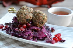 Spicy meatballs on red cabbage salad. With pomegranate seeds Royalty Free Stock Image