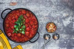 Spicy meatballs with tomato sauce. In cast iron pot, basil and parsley garnish. Top view, blank space stock images