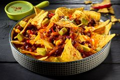 Spicy Mexican chili con carne au gratin. Topped with nachos and diced avocado pear and served with guacamole Stock Photography