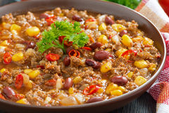 Spicy Mexican dish chili con carne in a brown pottery plate Stock Photos
