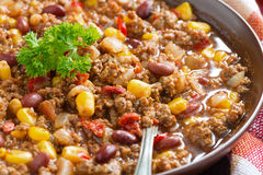 Spicy Mexican dish chili con carne in a brown pottery plate Royalty Free Stock Images