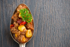 Spicy Mexican dish chili con carne in a spoon Stock Photos