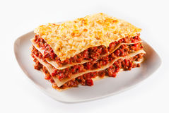 Spicy minced or ground beef lasagne. With sheets of traditional Italian noodles alternating with tasty meat served on a plate on white royalty free stock image
