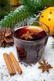 Spicy mulled wine in the glass in the snow, vertical Royalty Free Stock Images