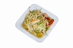 Spicy papaya salad on the plate. Spicy tomato sauce, roasted peanuts, lentils Royalty Free Stock Images