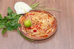Spicy papaya salad or Som Tum in Thailand on wooden plate. With vegetable stock images