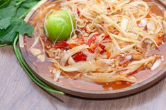 Spicy papaya salad or Som Tum in Thailand on wooden plate. With vegetable stock photography