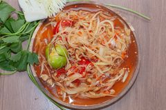 Spicy papaya salad or Som Tum in Thailand on wooden plate. With vegetable stock photos