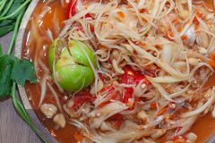 Spicy papaya salad or Som Tum in Thailand. On wooden plate with vegetable royalty free stock photography