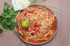 Spicy papaya salad or Som Tum in Thailand on wooden plate. With vegetable royalty free stock photography