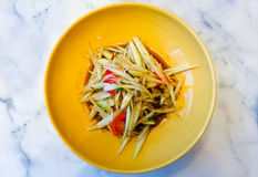 Spicy papaya salad with Thai anchovy sauce. Spicy green papaya salad with Thai anchovy sauce Traditional Thai food on yellow plate Stock Photo