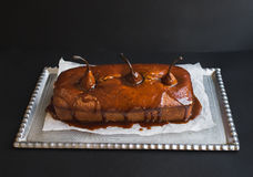 Spicy pear cake with caramel topping on a silver dish on dark Stock Photography
