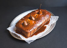 Spicy pear cake with caramel topping on a silver dish on a dark Stock Photography