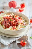 Spicy penne bolognese with bacon and herbs Royalty Free Stock Photos