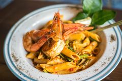 Spicy penne past with shrimp and basil. Penne spaghetti spicy with tiger prawn, penne spaghetti tom yam kung Stock Images
