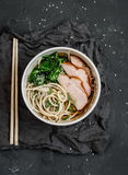 Spicy pork and noodle soup. On a dark background Royalty Free Stock Image