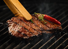 Spicy portion of seared steak grilling on a BBQ. Seasoned with fresh rosemary and a hot red chili pepper pod being lifted in a pair of wooden tongs Royalty Free Stock Photos