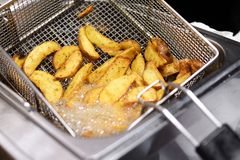 Spicy potato chips or wedges in a deep fryer Royalty Free Stock Photography