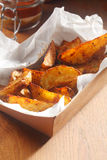 Spicy Potato Wedges on Cardboard Box Stock Image