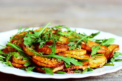 Spicy potatoes with arugula on a plate. Roasted potatoes with fresh arugula and simple dry seasoning mix Stock Photos