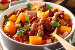 Spicy pumpkin chili soup with beef, tomatoes and red beans macro Stock Photos