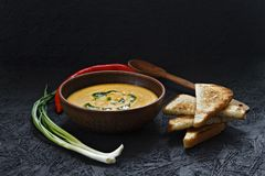 Spicy pumpkin cream soup with toast in a clay plate. stock photo